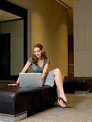 Woman using laptop in lobby