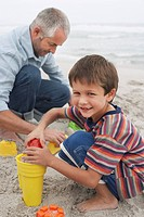 Father and son 5_6 playing in sand on beach