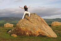 Woman stretching on a rock