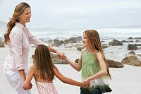 Mother playing with two daughters 7_9 10_12 on beach