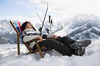Skier resting on deckchair in mountains