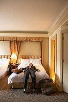Businesswoman lying on the bed in a hotel room