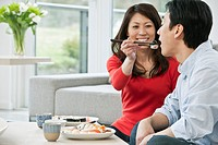 Middle_aged couple feeding each other sushi