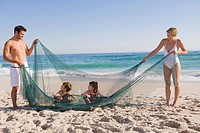 Family playing with a fishing net on the beach