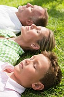 Boy with his parents lying on grass in a park