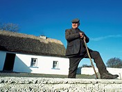 Co Galway,Ireland,Farmer stands outside his thatched cottage