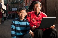 Grandfather and grandson using laptop in China Town, New York City