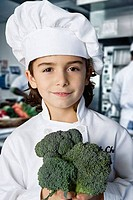 Boy holding a broccoli in the kitchen