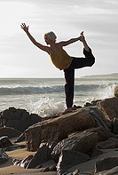 Mature woman in yoga position on shoreline