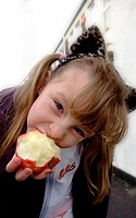5 year girl eating an apple in the street