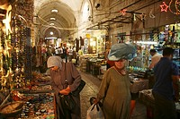 A Muslim woman with many bags carries one on her head, at a market in the old city section of Jerusalem