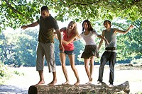 Four young people balancing on a log in a park