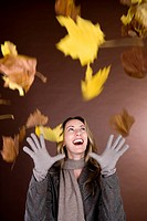 A mid adult woman smiling at falling autumn leaves