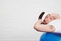 Overweight Man doing sit_ups on Exercise Ball