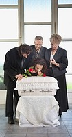 family grieving at an infant´s coffin