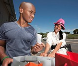 Man questioning bill of womans shopping bags, KwaZulu Natal Province, South Africa