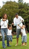 family lifestyle scene of a mum and dad with their two kids having fun with a hose pipe