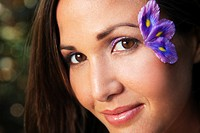 Hawaii, Oahu, Beautiful Young portrait of female with purple floral petals near her eye.