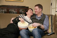 Snacking while lounging on the sofa at home is a fun pastime of otherwise busy couples  Pictured here is a couple snacking on popcorn and potato chips...