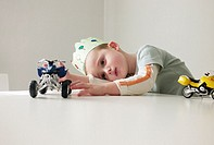 Boy with a crown in his birthday playing with cars on a table.
