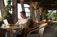 Caucasian man typing on laptop in restaurant