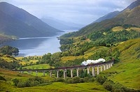 The Jacobite Steam Train, better known now as the Harry Potter Train, crossing the viaduct of Glenfinnan with loch Shiel in the background. Scotland. ...