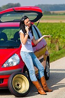Young woman with a tire breakdown at car