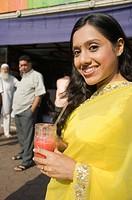 Woman drinking juice at a market stall, Mumbai, Maharashtra, India