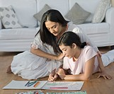 Girl making a drawing with her mother sitting beside her