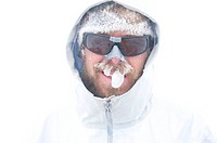A mountaineer and skier has his beard covered in rime, looking like an icicle, deep in the backcountry of Chile´s Darwin Range