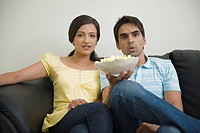Couple watching television and eating popcorn