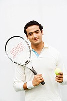 Portrait of a young man holding a tennis ball and a tennis racket