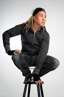 Asian man with dreadlocks crouching on a stool