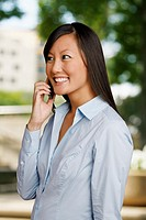 An Asian woman speaks into her cell phone