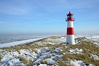 Lighthouse List East on snow covered dunes with a bright blue sky at a sunny day with icy sea in the background, Sylt, Northfrisian Islands, Schleswig...