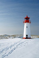 Lighthouse List West on snow covered dunes showing tracks of people leading to the lighthouse, with a bright blue sky at a sunny day, Sylt, Northfrisi...