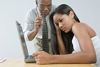 Male teacher instructing his student sitting in front of a laptop