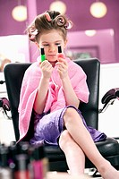 portrait of young girl at hair salon with two different nail polishes