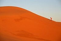 Person climbing a dune in Erg Chebbi, Merzouga, Morocco