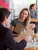 Man and woman looking at menus in restaurant