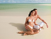 Couple sitting with eyes closed on beach