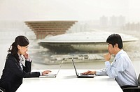 Business colleagues at desk with laptops facing each other