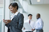 Black businesswoman text messaging on cell phone