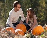 Father and daughter in pumpkin patch