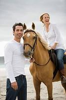 Brown horse, man, woman, beach, sea, sand