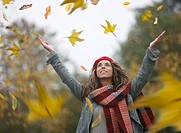 Woman throwing dried leaves into air