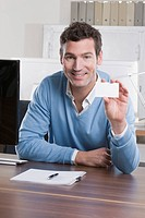 Germany, Munich, business man in office holding business card, smiling, portrait