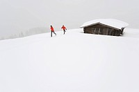 Italy, South Tyrol, Couple cross_country skiing next to cabin