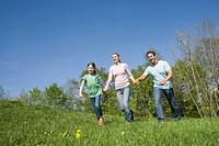 Germany, Bavaria, Munich, Family walking in meadow