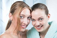 Germany, Bavaria, Munich, Two young women in spa, smiling, portrait